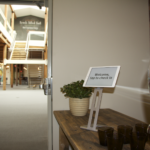 Shot of the entryway to a Fresh Tilled Soil office with a water tank for guests, an iPad that says
